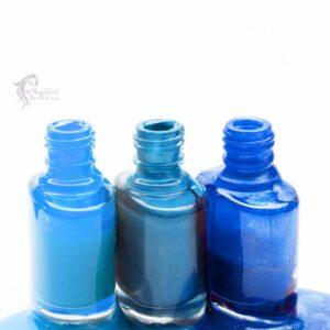 blue-shades-nail-polish-spilled-around-three-opened-bottles